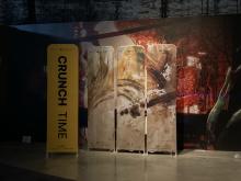 wnętrze dużego pomieszczenia, a w nim stojące panele z nazwą wydarzenia i barwnym obrazem