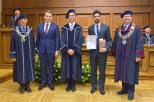 Na zdjęciu się pięciu mężczyzn, w tym prof. Krzysztof Wilde Rektor PG oraz absolwent inż. Cezary Swinarski.  Dwóch mężczyzn ubranych jest w garnitury, trzech w togi. Mężczyźni stoją w auli.