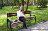Na zdjęciu znajduje się uśmiechnięta mgr inż. Agnieszka Mikołajczyk siedząca na drewnianej ławce. Kobieta ubrana jest w jasną marynarkę i jasną koszulę oraz czarną spódnicę i czarne rajstopy. Ma długie rozpuszczone włosy i okulary.