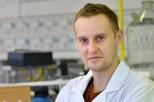 Na zdjęciu znajduje się dr inż. Mariusz Szkoda ubrany w bordową koszulkę i biały fartuch. Mężczyzna stoi w laboratorium na tle sprzętu do badań.