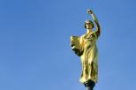 Zdjęcie przedstawia rzeźbę Alegorii Nauki w kolorze złotym, która wieńczy wieżę zegarową gmachu głównego Politechniki Gdańskiej na tle niebieskiego nieba