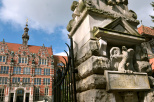 Na zdjęciu widoczny fragment bramy głównej z napisem Politechnika Gdańska z orłem. W tle gmach główny Politechniki Gdańskiej
