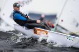 Na zdjęciu znajduje się Filip Ciszewski wicemistrz Europy seniorów w olimpijskiej klasie Laser Radial. Znajduje się w żaglówce na morzu wśród fal.