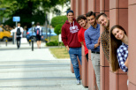 Zdjęcie przedstawia grupę studentów wyglądających zza filarów budynku