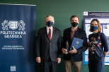 The photo shows the laureate of M.Sc. Patryk Blaszczak in the company of prof. dr hab. Józef Sienkiewicz and the supervisor, dr hab. Eng. Beata Bochentyn. Everyone is standing next to each other against the background of a green wall and a navy blue banner with the Gdańsk University of Technology. All are dressed in dark.