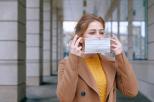 Na zdjęciu młoda kobieta zakładająca maseczkę