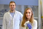 Na zdjęciu znajduje się mgr inż. Zuzanna Zarach, która otrzymała nagrodę oraz promotor dr inż. Mariusz Szkoda. Obydwoje ubrani są w białe kitle. Obydwoje mają blond włosy, kobieta o długości za ramiona.