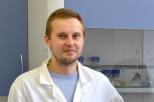 na zdjęciu widoczny jest dr inż. Mariusz Szkoda ubrany w biały kitel oraz jasno niebieską bluzkę.