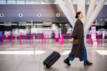 Obraz przedstawia lotnisko, halę przylotów. Na pierwszym planie widać idącą kobietę z walizką na kólkach.