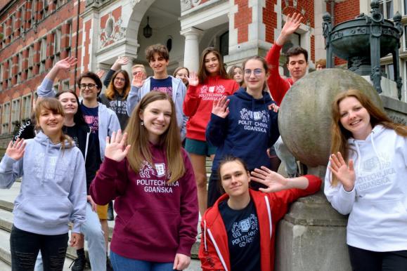 grupa uśmiechniętych studentów przed gmachem głównym PG