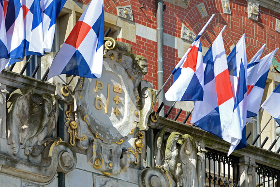 Kartusz i flagi wiszące nad wejściem do Gmachu Głównego