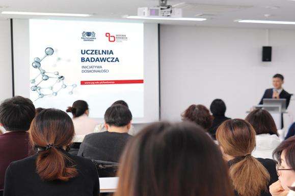Zdjęcie przedstawia osoby oglądające prezentację na dużym ekranie