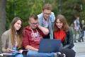 na zdjęciu grupa uśmiechniętych studentów na terenie kampusu PG (dwie studentki i student siedzą na ławce, student trzyma na kolanach laptopa. Za jego plecami stoi kolejny student, którzy przygląda się obrazowi wyświetlanemu na laptopie)