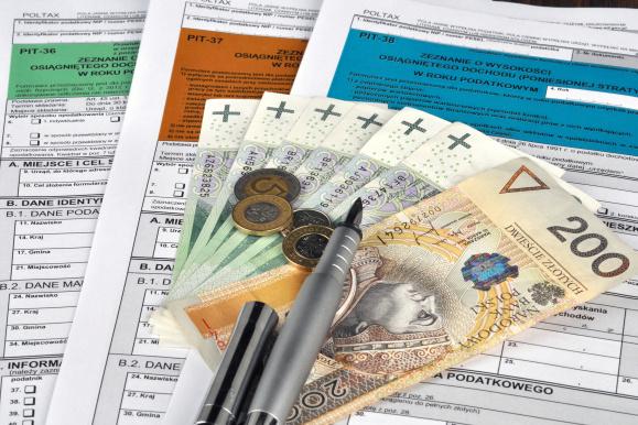 Rozliczenia PIT, banknoty, monety i pióro